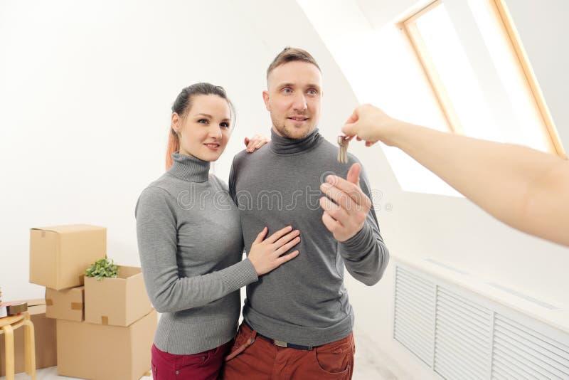 O vendedor dá a clientes as chaves ao apartamento novo imagem de stock