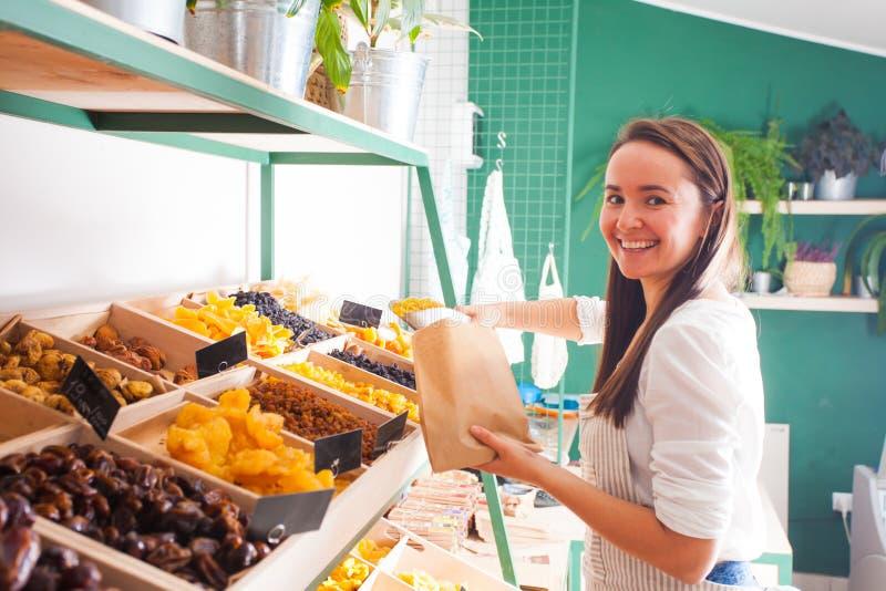 O vendedor da jovem mulher embala frutos secados na loja de mantimento foto de stock royalty free