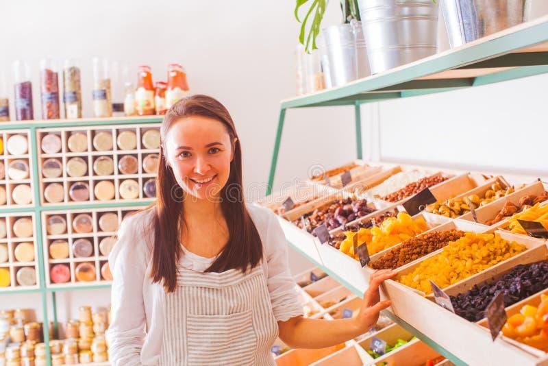 O vendedor da jovem mulher toma frutos secos do contador da loja fotografia de stock
