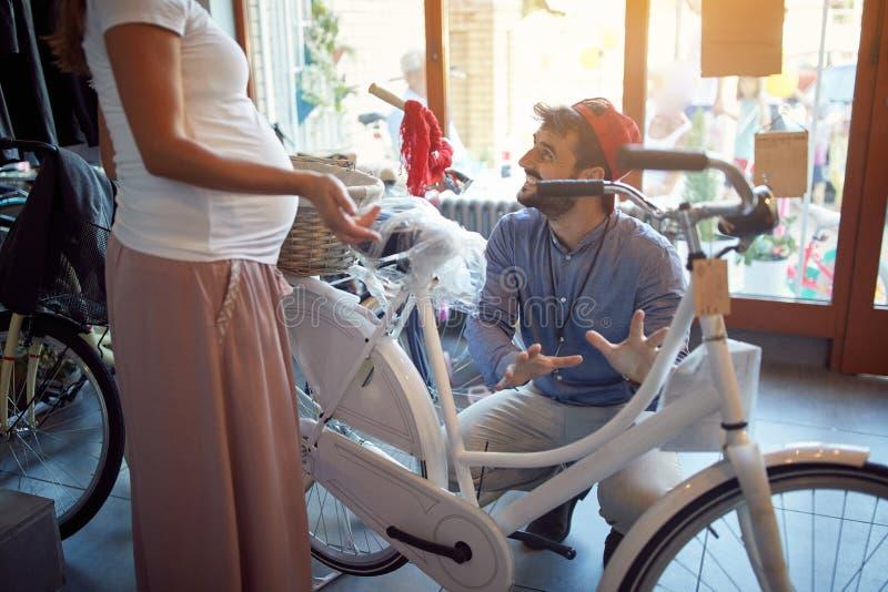 O vendedor de sorriso do homem est? ajudando a mulher a escolher a bicicleta nova na loja da bicicleta imagem de stock