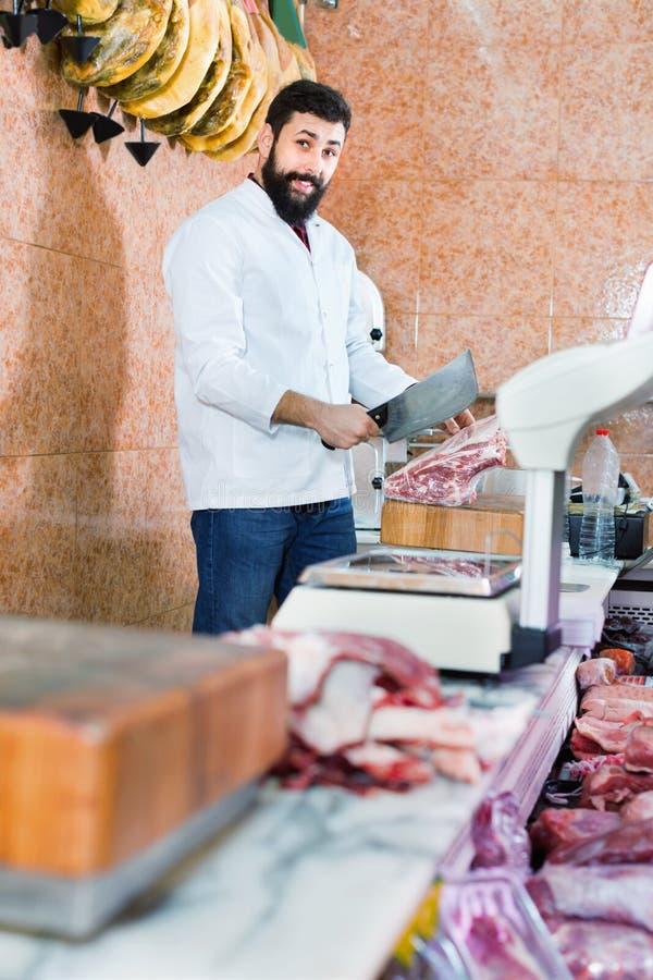 O vendedor do homem que prepara a carne para vender nos butcher's compra foto de stock