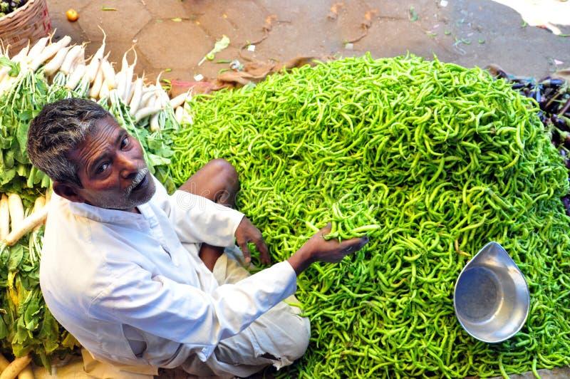 O vendedor dos pimentões que faz o negócio em um mercado asiático dos vegetais fotografia de stock