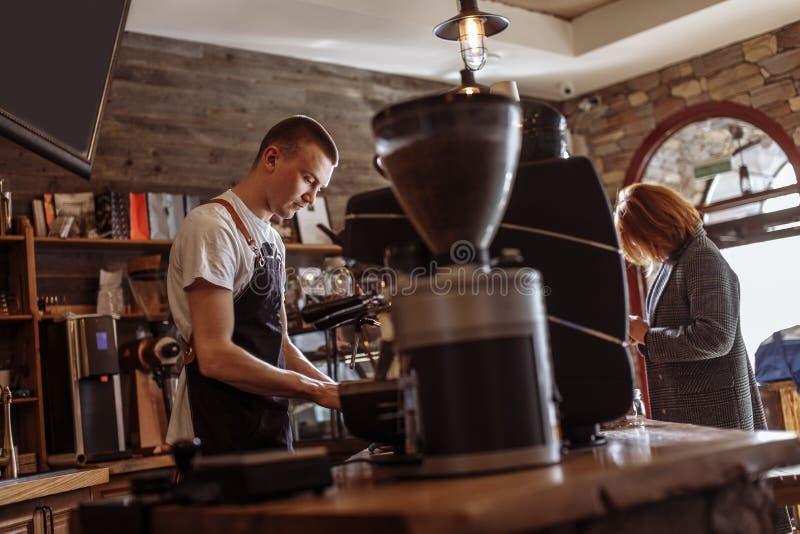 O vendedor está fazendo o café para a mulher fotografia de stock