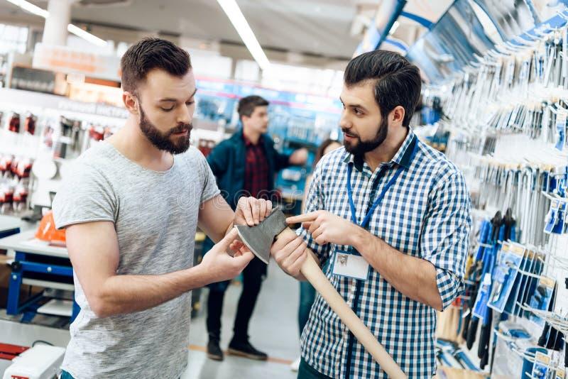 O vendedor está mostrando a cliente farpado o machado novo na loja das ferramentas elétricas imagem de stock royalty free