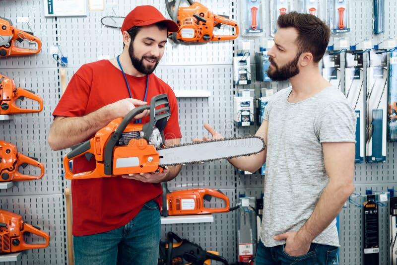 O vendedor está mostrando a cliente farpado a serra de cadeia nova na loja das ferramentas elétricas fotografia de stock