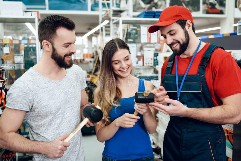 O vendedor está mostrando pares de martelos de borracha novos dos clientes na loja das ferramentas elétricas fotografia de stock royalty free