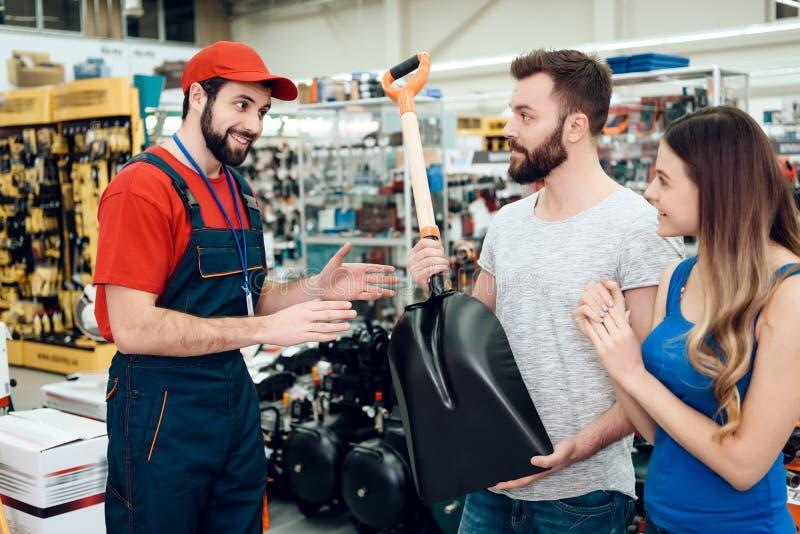 O vendedor está mostrando pares de showel novo dos clientes na loja das ferramentas elétricas fotografia de stock royalty free