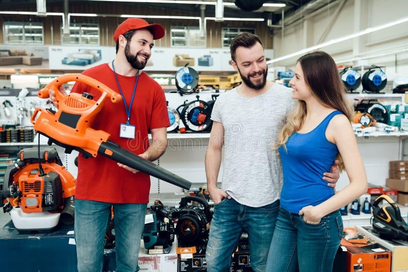 O vendedor está mostrando pares de ventilador de folha novo dos clientes na loja das ferramentas elétricas fotografia de stock