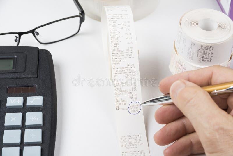 O vendedor está verificando recibos do caixa para ver se há o lucro ou a perda fotos de stock