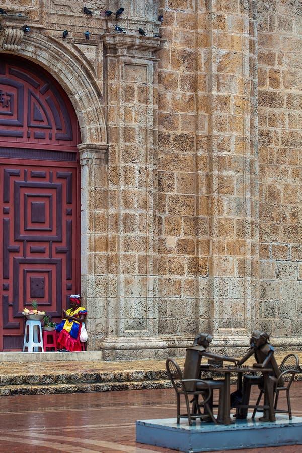 O vendedor fêmea dos frutos tradicionais da rua chamou Palenquera e os jogadores de xadrez estátua no quadrado de San Pedro Clave imagens de stock royalty free