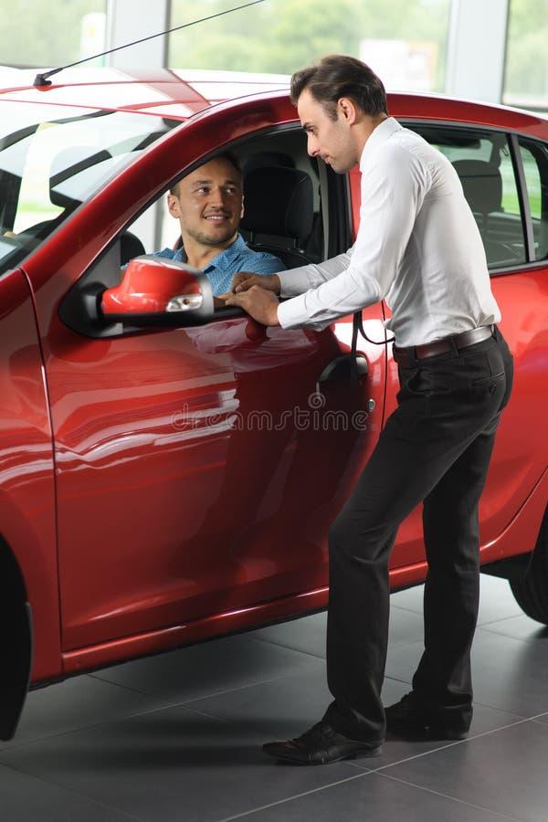 O vendedor mostra o carro para o cliente imagens de stock royalty free