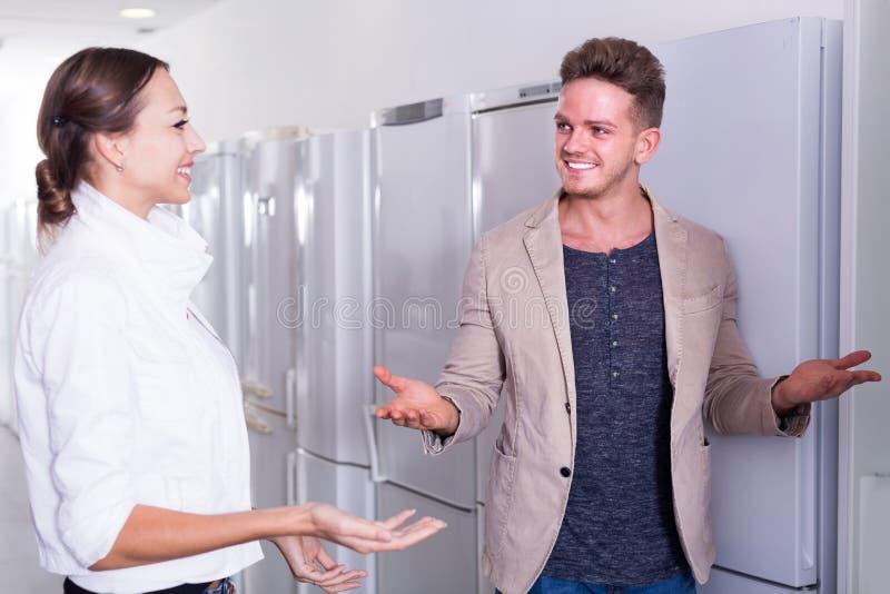 O vendedor oferece a uma ajuda da jovem mulher comprar o refrigerador da cozinha foto de stock