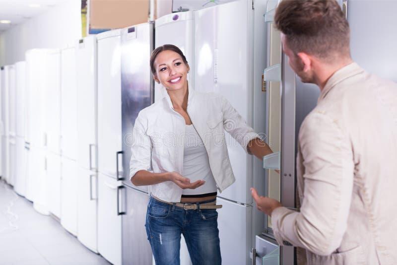 O vendedor oferece a uma ajuda do cliente comprar o refrigerador foto de stock royalty free