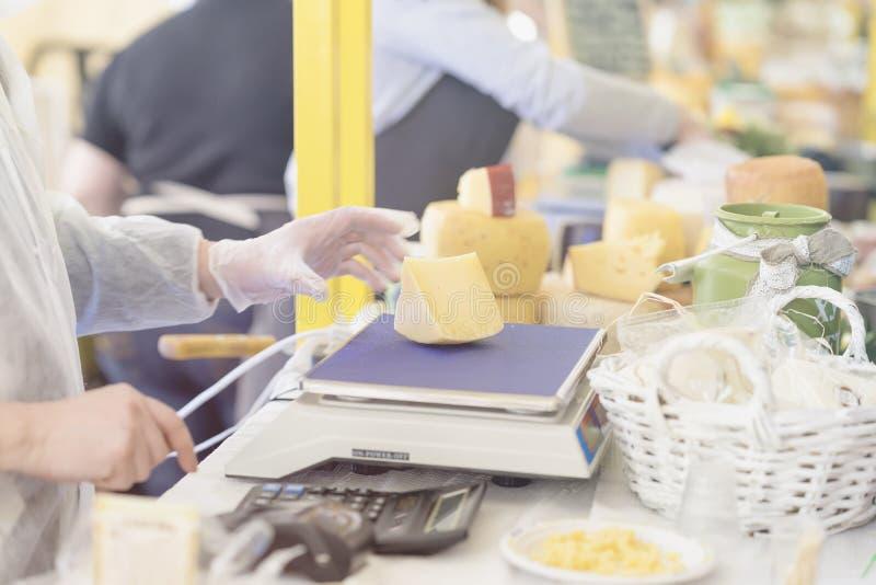 O vendedor pesa a parte de queijo fresco do fazendeiro no mercado de produtos orgânicos, foco seletivo Produto de leiteria gastro imagens de stock royalty free