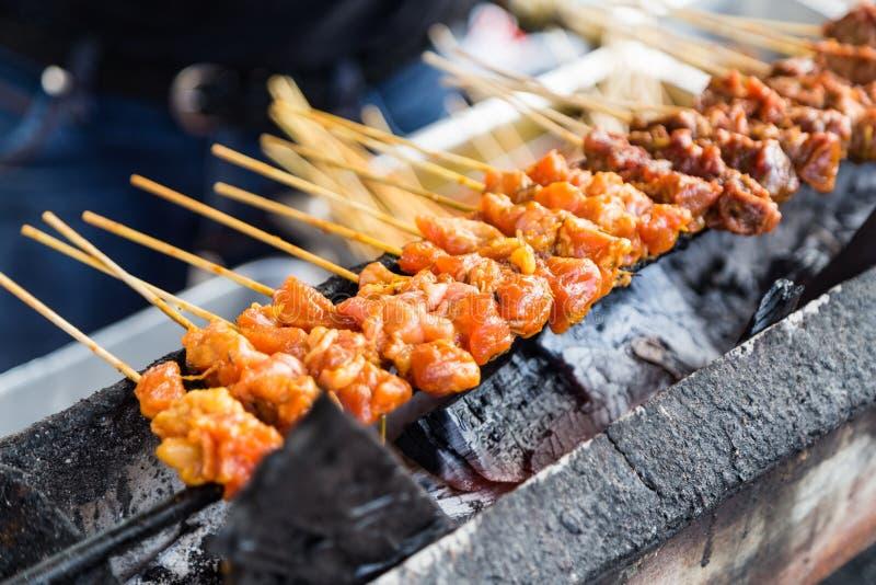 O vendedor que preparam a galinha e a carne assam satay no gri do carvão vegetal fotografia de stock