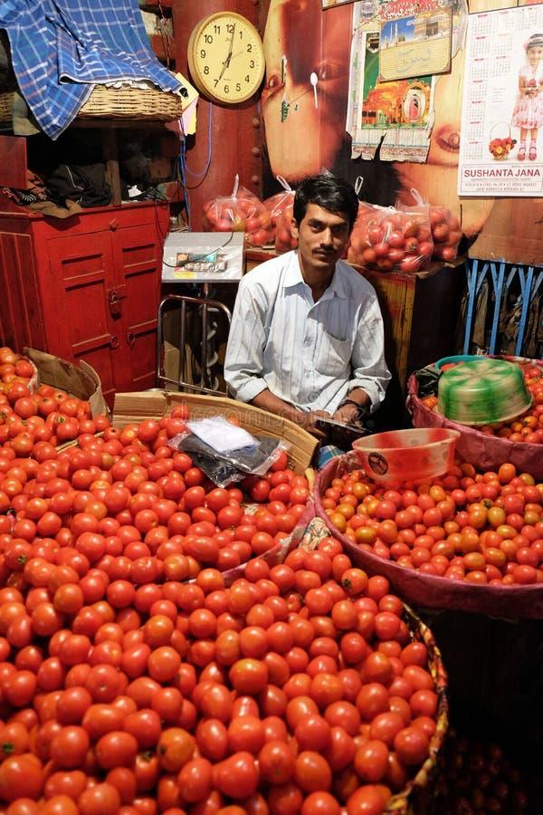 O vendedor senta-se atrás de uma grande pilha dos tomates no novo mercado em Kolkata foto de stock royalty free