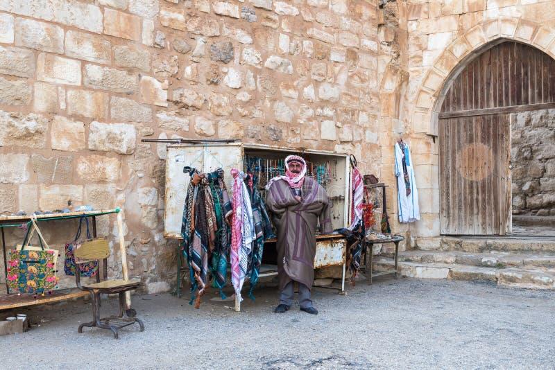 O vendedor - um árabe está perto de sua loja com as lembranças perto da entrada à fortaleza medieval Ash Shubak, estando em um mo foto de stock royalty free