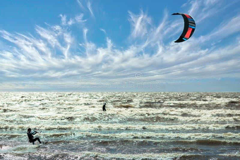 O vento e o papagaio surfam o céu bonito da competição no fundo imagem de stock