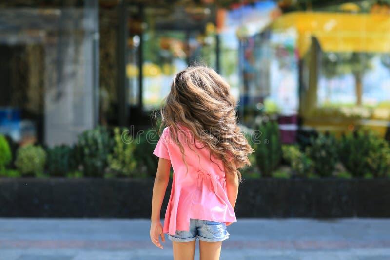O verão da criança da forma na cidade está em um streetl Menina na moda nos óculos de sol que estão na rua no por do sol imagens de stock royalty free