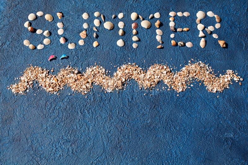 O verão da palavra fez das conchas do mar, onda do mar, areia dourada, dois golfinhos de salto no fim azul da opinião superior do fotos de stock