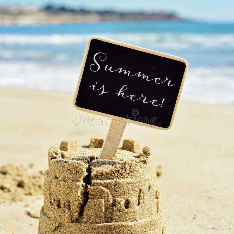 O verão do texto está aqui em um quadro indicador que cobre um castelo de areia fotos de stock