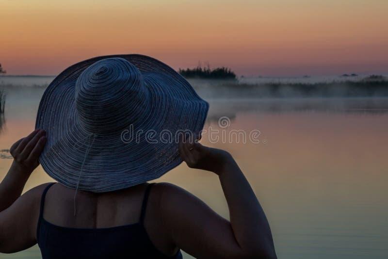 O verão, férias, um nascer do sol bonito sobre a superfície da água, uma mulher bonita em um chapéu elegante, olhando o alvorecer foto de stock royalty free