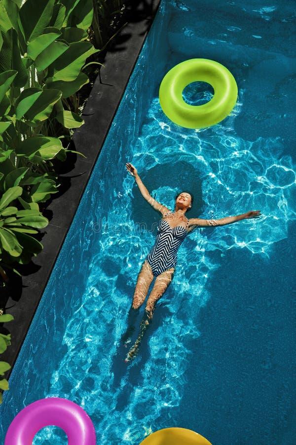 O verão relaxa Mulher que flutua, água da piscina Feriado do verão foto de stock royalty free