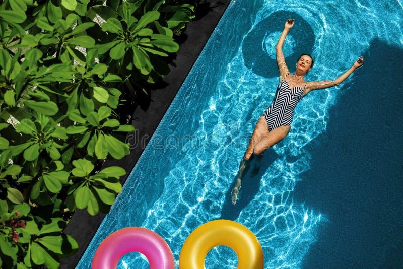 O verão relaxa Mulher que flutua, água da piscina Feriados do verão imagem de stock