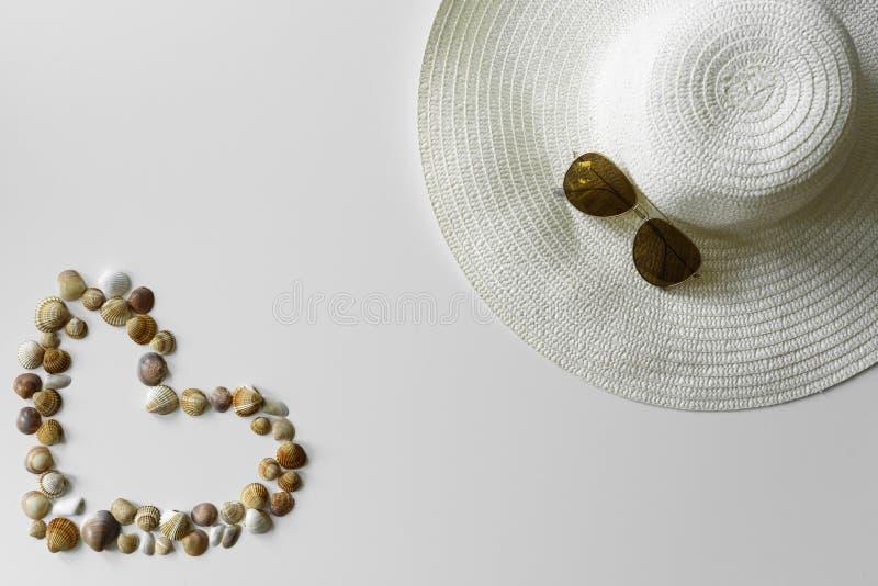 O verão setup das conchas do mar, do chapéu do verão e dos óculos de sol imagens de stock