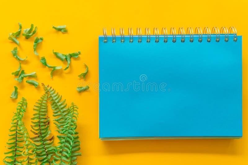 O verde azul do caderno sae mínimo no fundo amarelo imagem de stock royalty free