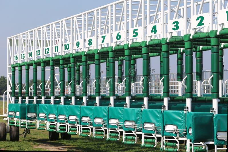 O verde coloriu portas do começo para as corridas de cavalos na pista imagens de stock royalty free