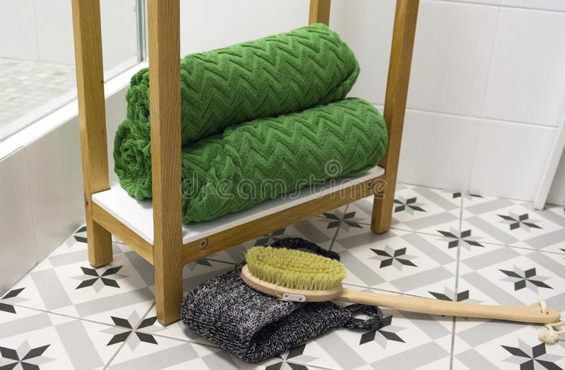 O verde dobrou belamente toalhas em uma prateleira branca com uma escova e uma toalha de rosto da massagem fotos de stock royalty free