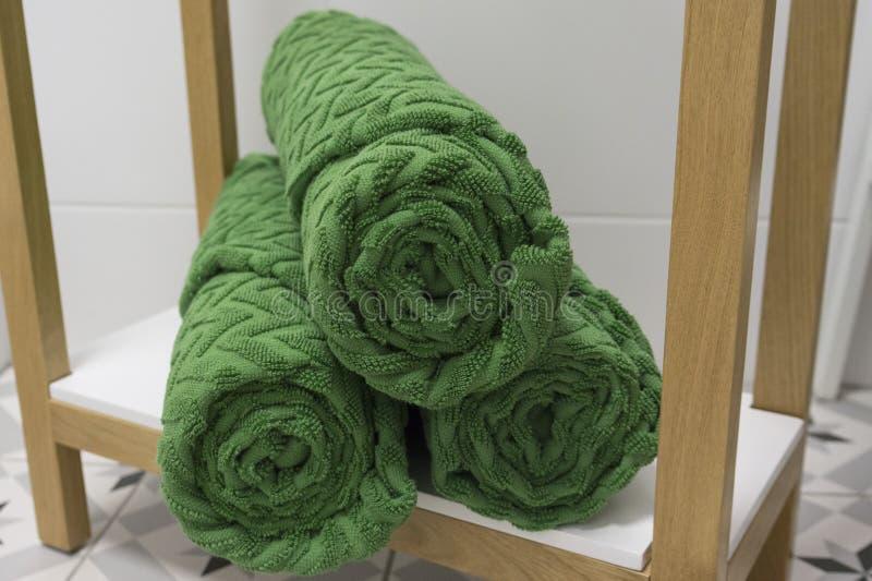 O verde dobrou belamente toalhas em uma prateleira branca contra uma telha branca fotos de stock