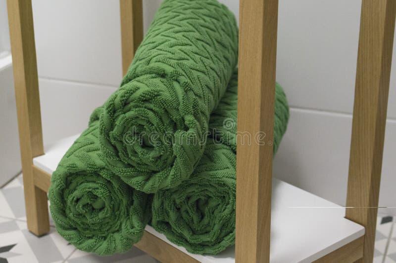 O verde dobrou belamente toalhas em uma prateleira branca contra uma telha branca fotos de stock royalty free