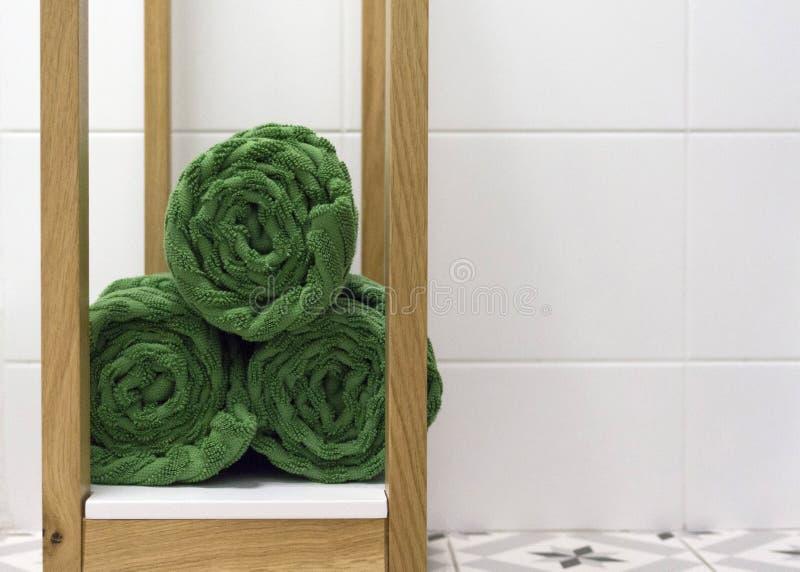O verde dobrou belamente toalhas em uma prateleira branca contra uma telha branca foto de stock royalty free