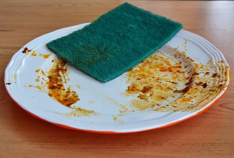 O verde esfrega a mancha do alimento da limpeza da esponja no prato branco foto de stock royalty free