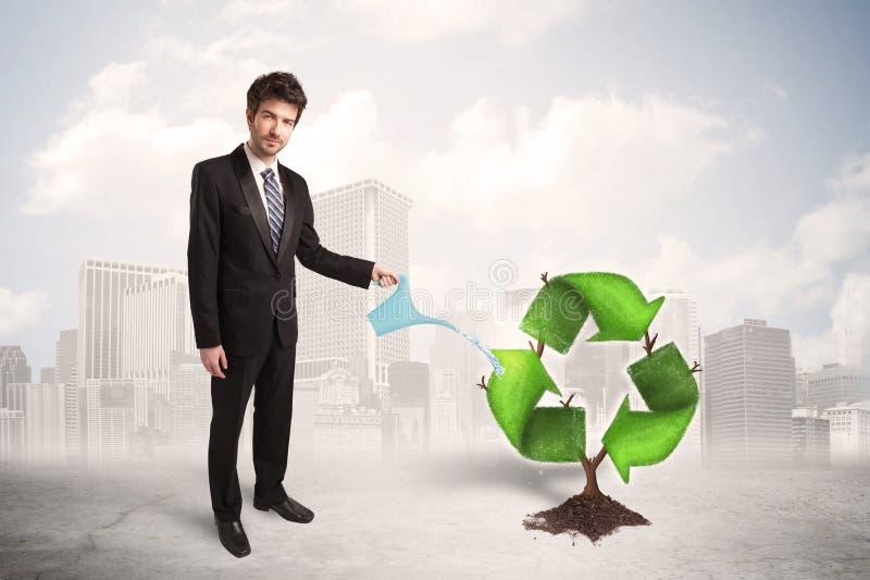 O verde molhando do homem de negócio recicla a árvore do sinal no fundo da cidade ilustração do vetor