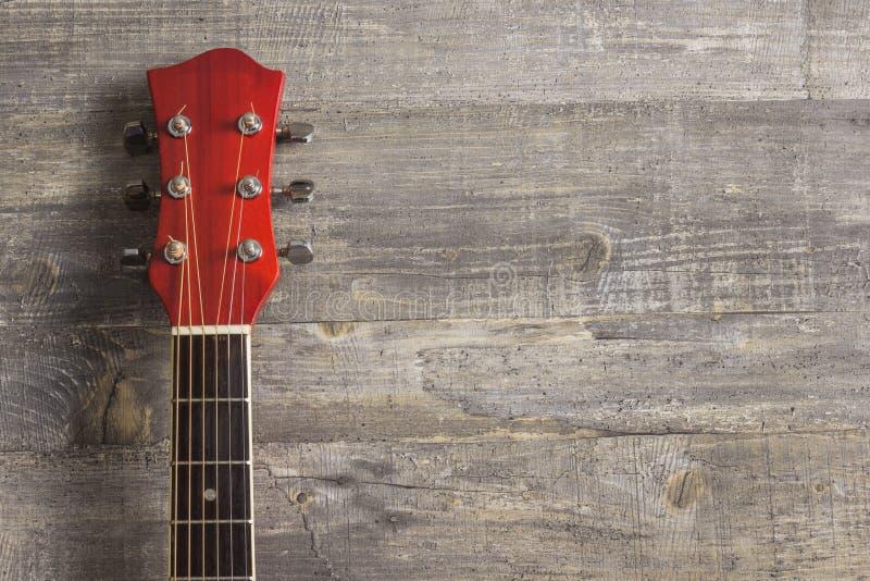 O vermelho acústico da guitarra, pescoço que encontra-se em um fundo do vintage da madeira no fundo do grunge velho embarca Lugar imagens de stock