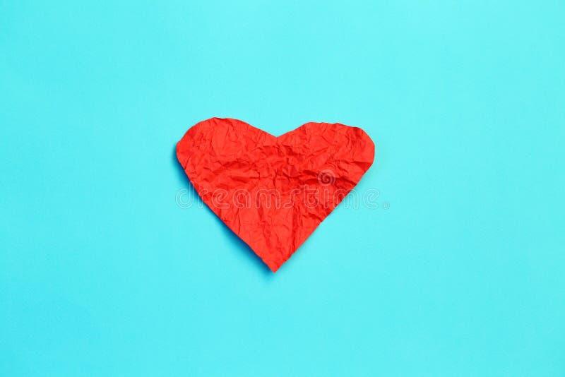O vermelho amarrotou os corações de papel no fundo azul, dia de Valentim fotos de stock royalty free