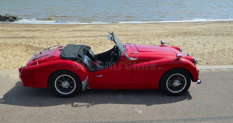 O vermelho clássico MGA abre o carro superior dos esportes estacionado no passeio da frente marítima imagens de stock royalty free