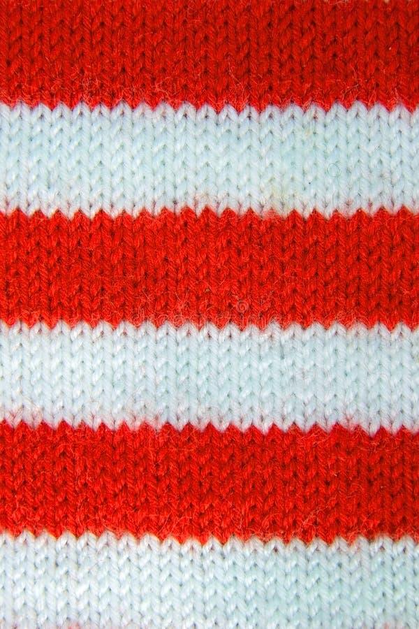 O vermelho colorido do Natal, branco fez malha o teste padrão do chapéu do ajudante de Papai Noel foto de stock royalty free