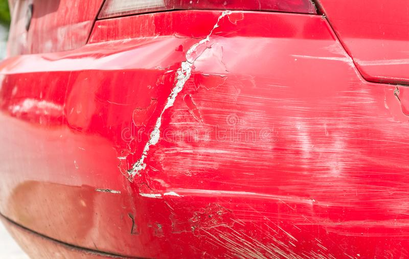 O vermelho danificou o carro no acidente do impacto com pintura riscada e amolgou o corpo do metal do amortecedor traseiro fotografia de stock royalty free