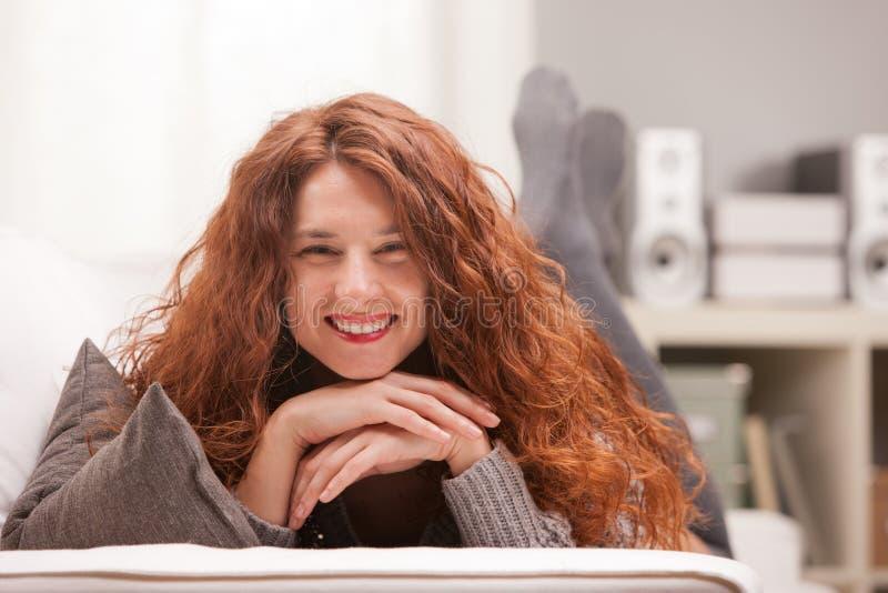 O vermelho dirigiu a menina muito bonito que sorri em seu sofá imagem de stock royalty free