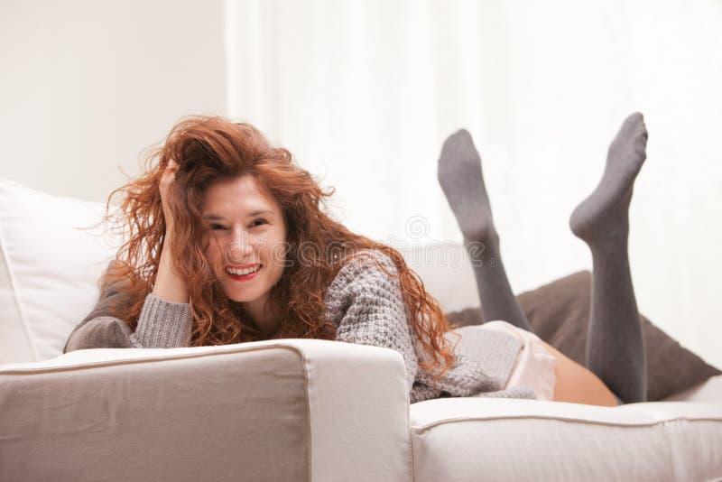 O vermelho dirigiu a menina muito bonito que sorri em seu sofá imagens de stock royalty free