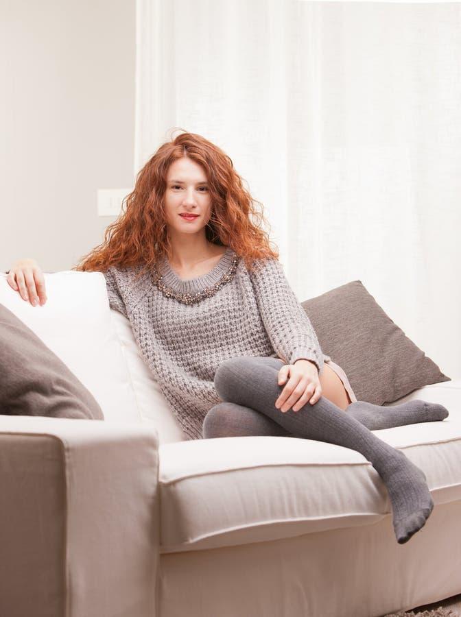 O vermelho dirigiu a menina muito bonito séria em seu sofá fotos de stock royalty free