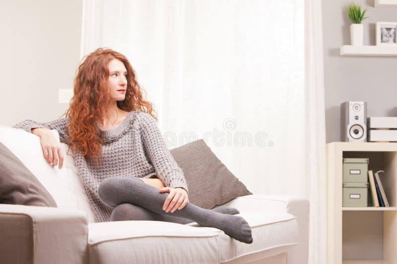 O vermelho dirigiu a menina muito bonito séria em seu sofá foto de stock