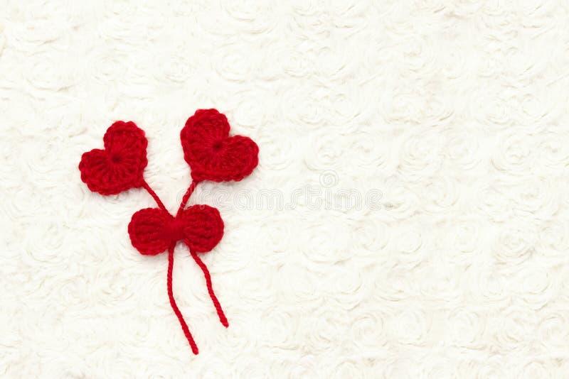 O vermelho dois faz crochê corações de lãs e a fita no branco faz crochê o fundo O conceito para o 14 de fevereiro, dia de são va fotografia de stock royalty free