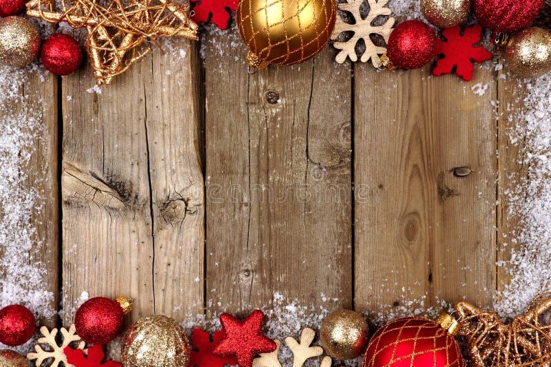 O vermelho e o Natal do ouro dobram a beira com neve na madeira imagem de stock