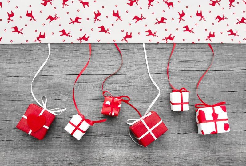 O vermelho e o White Christmas apresentam em um fundo de madeira na contagem foto de stock