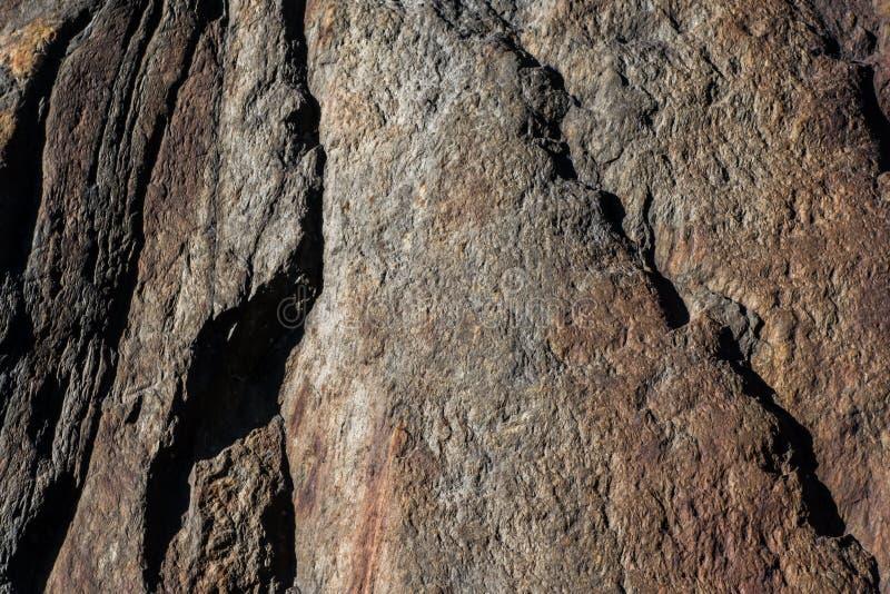 O vermelho matizou a rocha corroída do granito com quebras e diferenças na superfície s imagem de stock